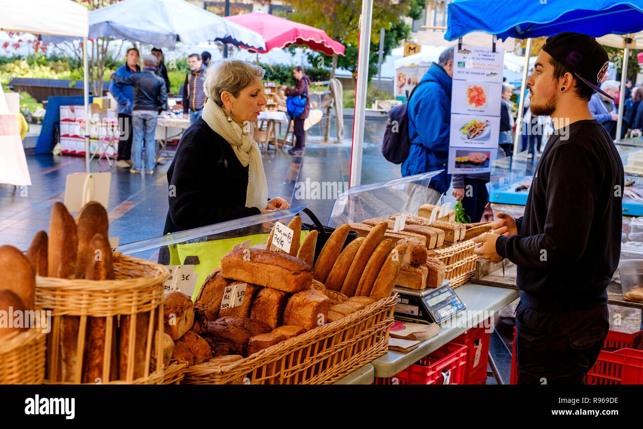 A shopper buying bread at an artisan baker stall in a street market in the Square Charles de Gaulle, Toulouse, France - Stock Image