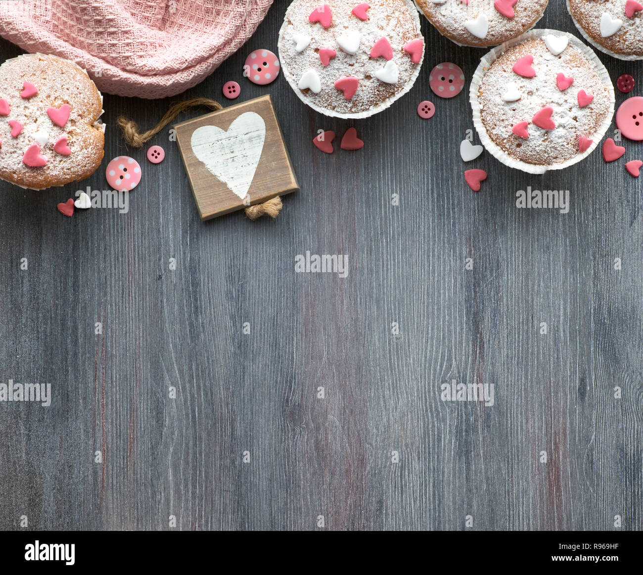 Sugar-sprinkled muffins with pink and white fondant icing hearts. Top view, plenty of copy-space. Birthday or Valentine concept. - Stock Image