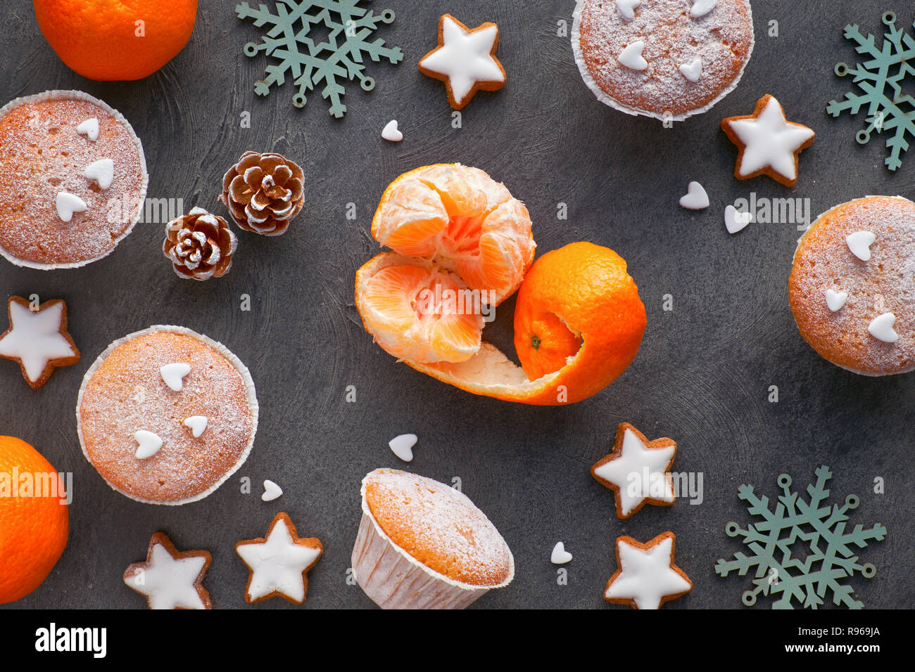 Top view of the table with satsumas, sugar-sprinkled muffins and Christmas star cookies on dark textured background - Stock Image