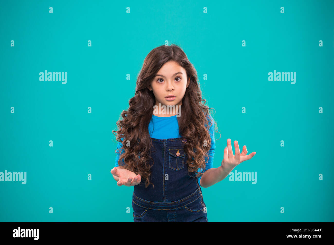 What are you talking about. Kid stunned bewildered emotion can not believe her eyes. Girl curly hairstyle wondering. Child bewildered stunned face blue background. Kid girl long curly hair stunned. - Stock Image