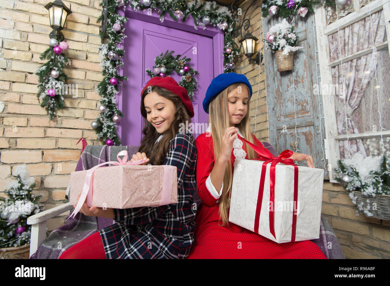 The only thing I like about Christmas is gift. Happy little girls unwrap  gift boxes cf8f5cbb7