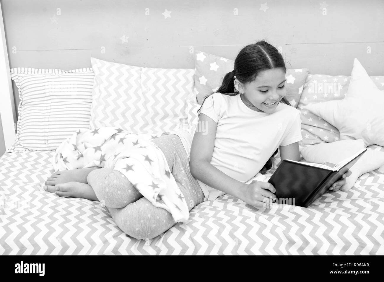 Fascinating story. Girl child lay bed with pillows read book. Kid prepare to go to bed. Time for evening fascinating story. Girl kid long hair cute pajamas relax and read fascinating story book. - Stock Image
