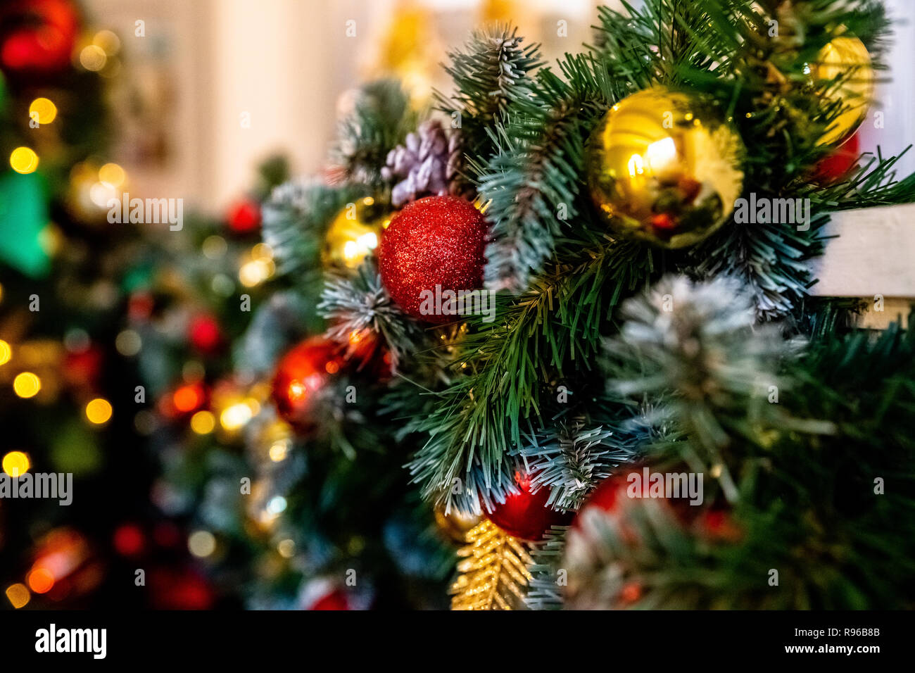 Decorative garland from christmas tree branches and cones. home decorated for winter holidays, little red and gold baubles. Copy space for wishes.Selective focus. Colorful christmas decorations.Happy new year.Home decor. - Stock Image