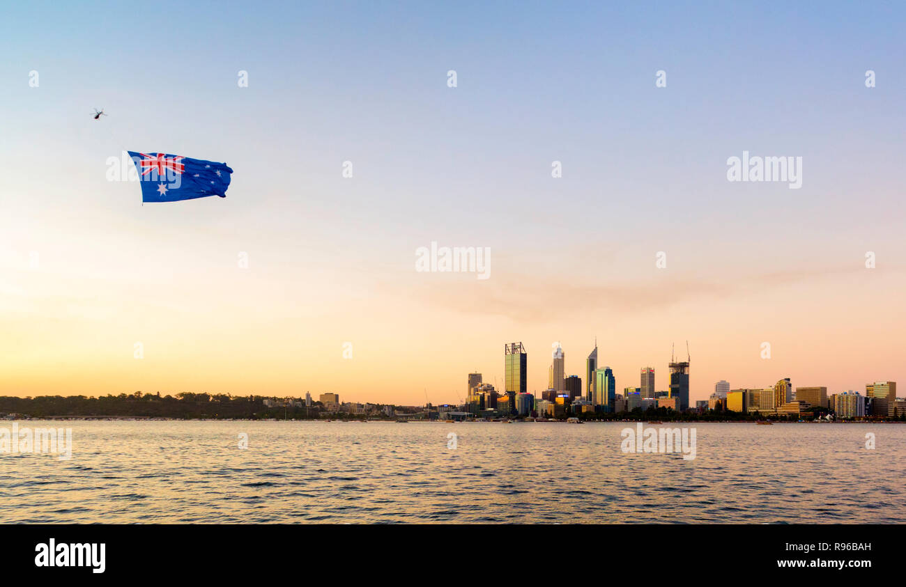 A large Australian flag being pulled by a helicopter over Perth city on Australia Day - Stock Image