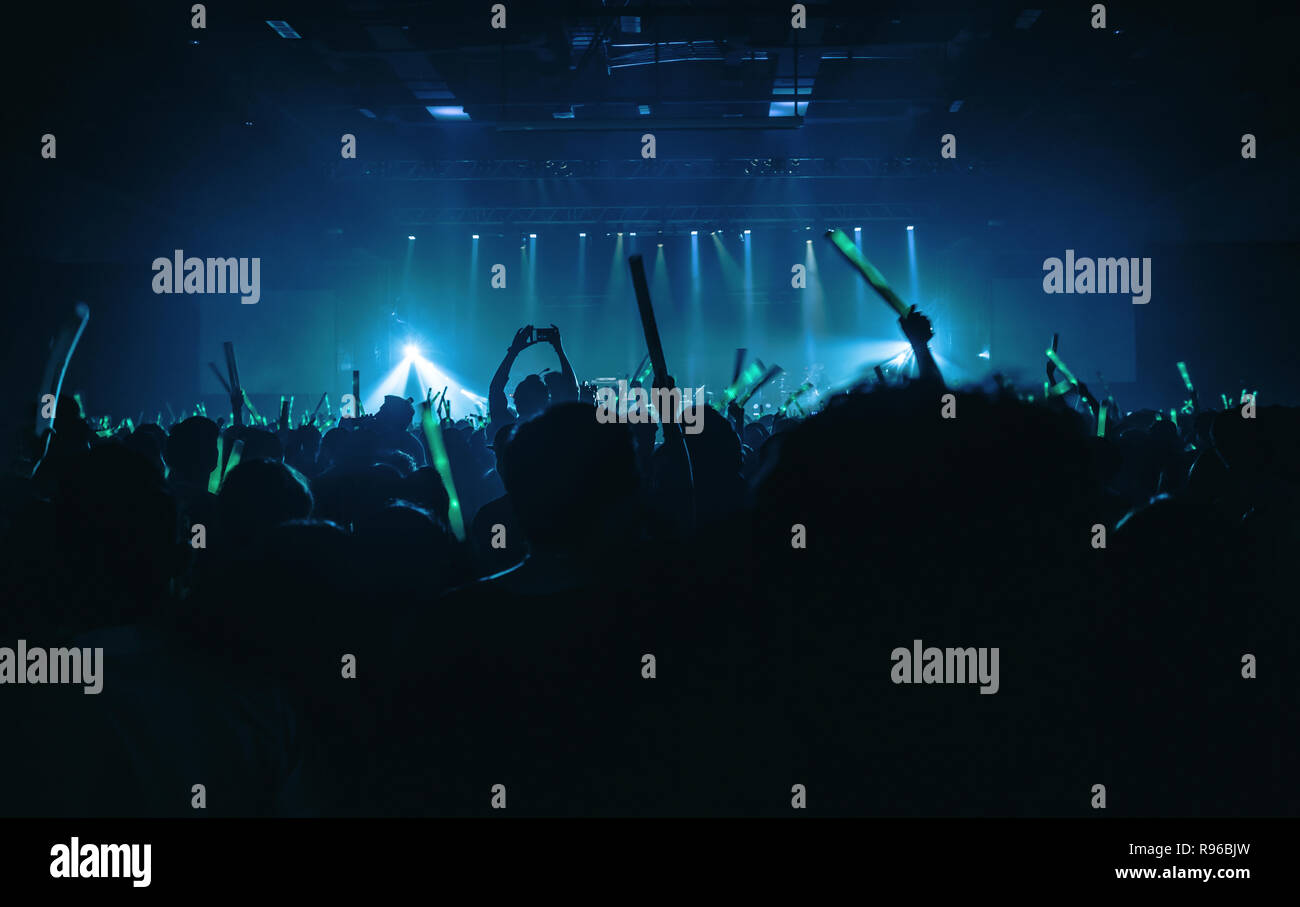 Silhouette audience crowd enjoy the club, raise hands and holding green light batons motion and use smart phone - Stock Image