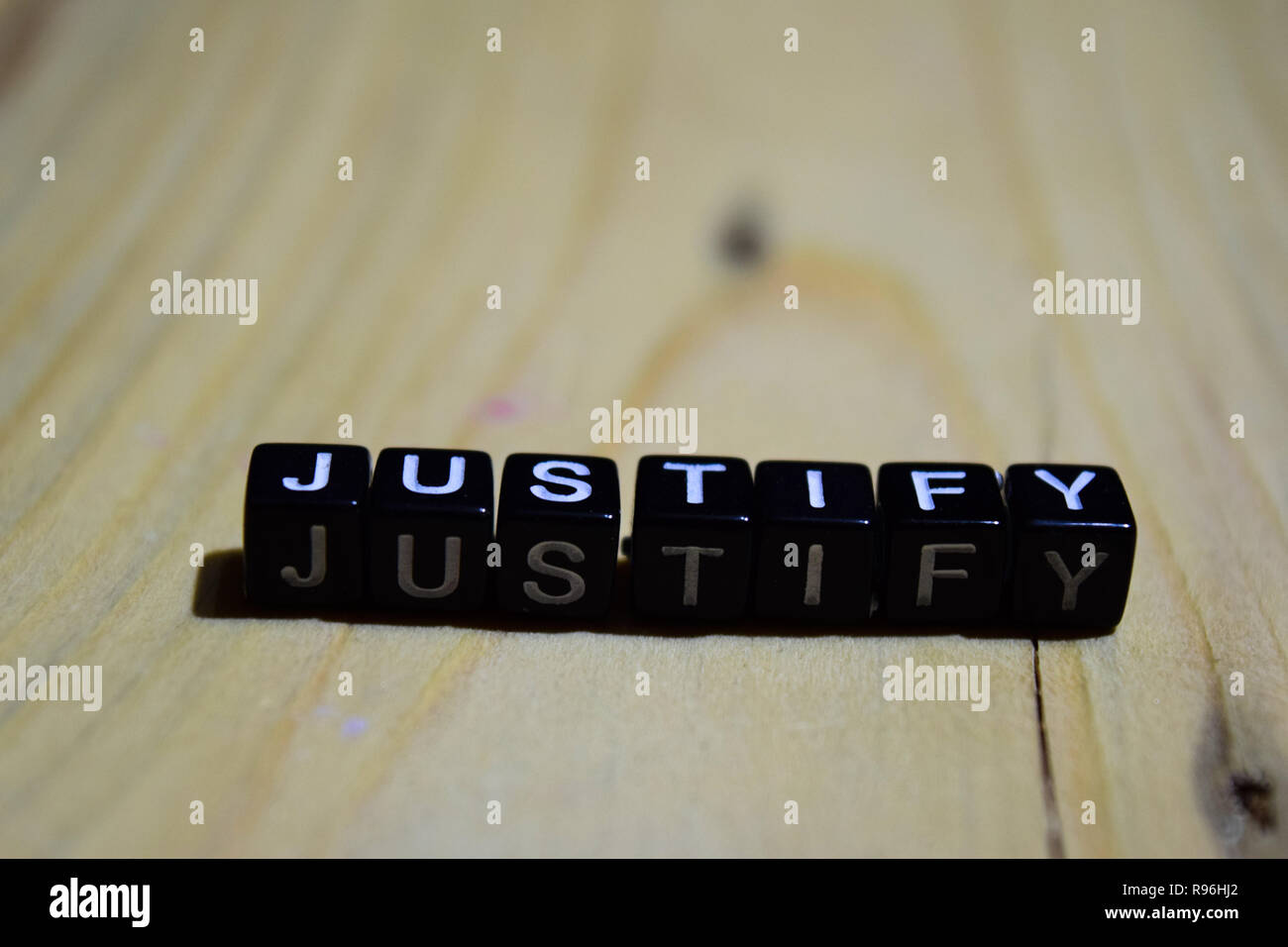 Justify written on wooden blocks. Inspiration and motivation concepts. Cross processed image on Wooden Background - Stock Image