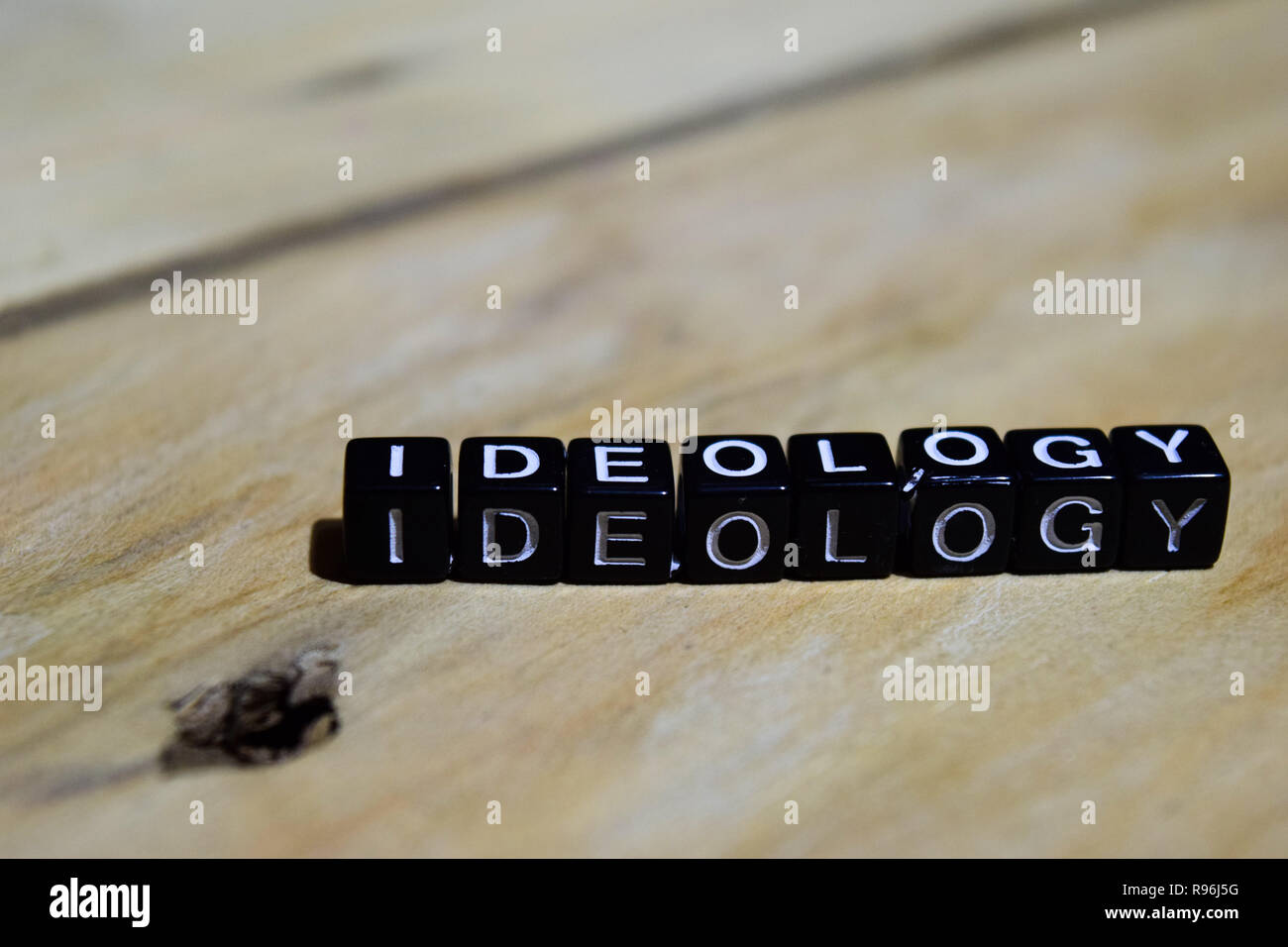 Ideology written on wooden blocks. Inspiration and motivation concepts. Cross processed image on Wooden Background - Stock Image