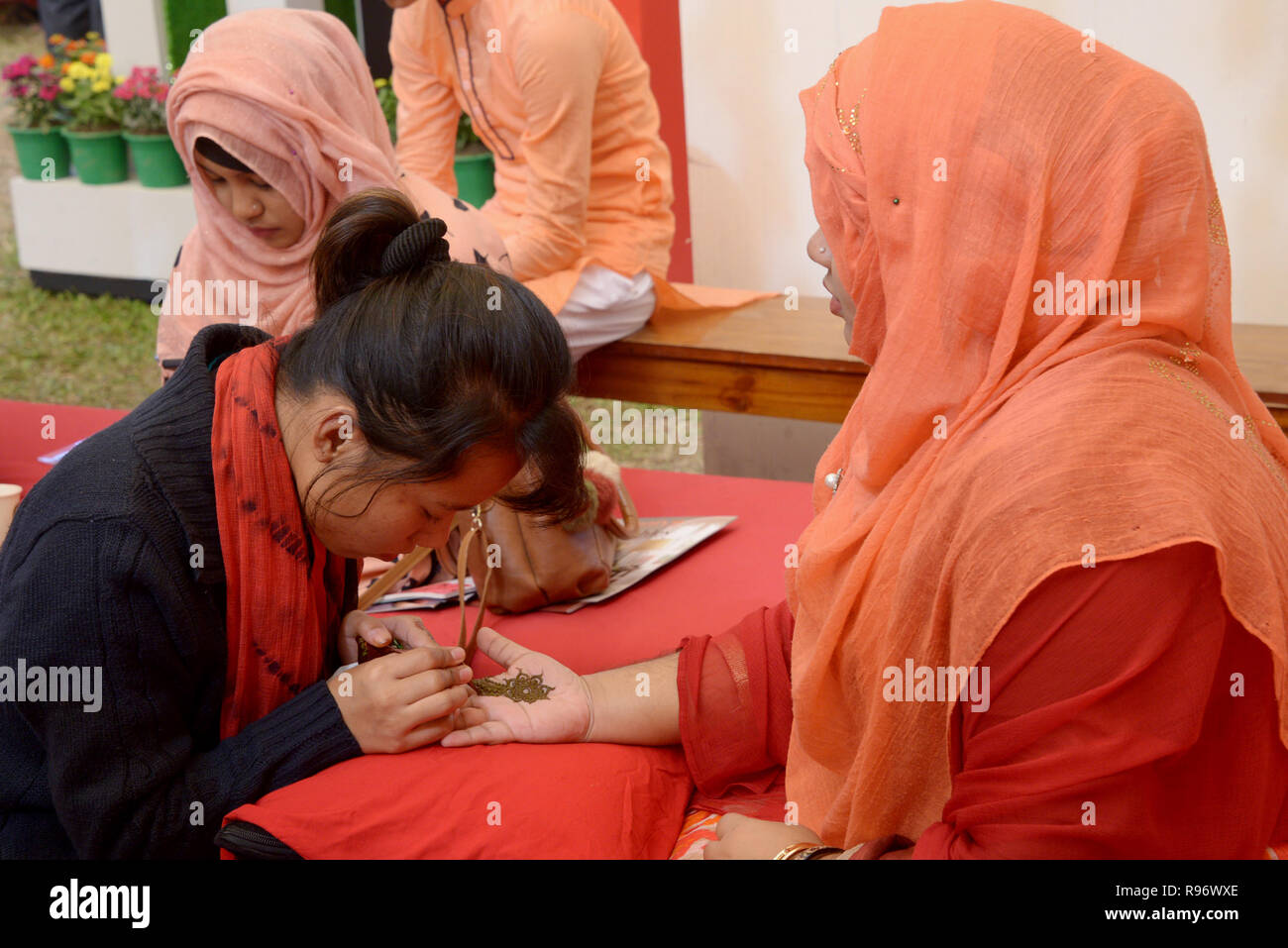 Dhaka. 20th Dec, 2018. A woman gets henna applied on her hand at a wedding fair in Dhaka, capital of Bangladesh, Dec. 20, 2018. In Bangladesh, women always have henna, a traditional India skin art, painted on their hands prior to attending a ceremony. Bangladesh entered the peak season from December to upcoming New Year as people in the country usually hold wedding ceremonies in winter. Credit: Xinhua/Alamy Live News - Stock Image