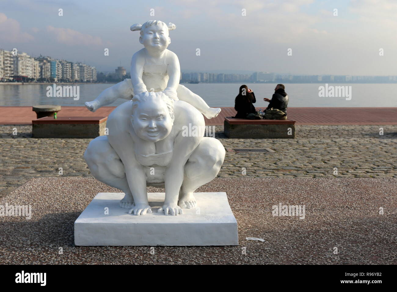 Thessaloniki, Greece  20th Dec 2018  People sit next to a statue by