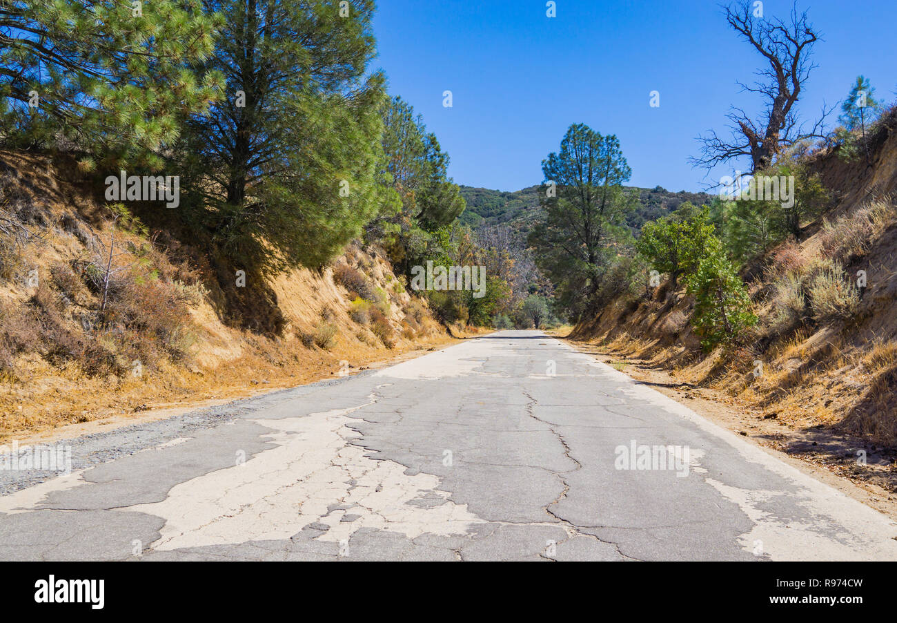 Cracked and rugged road leads through wooded hills in southern California. - Stock Image