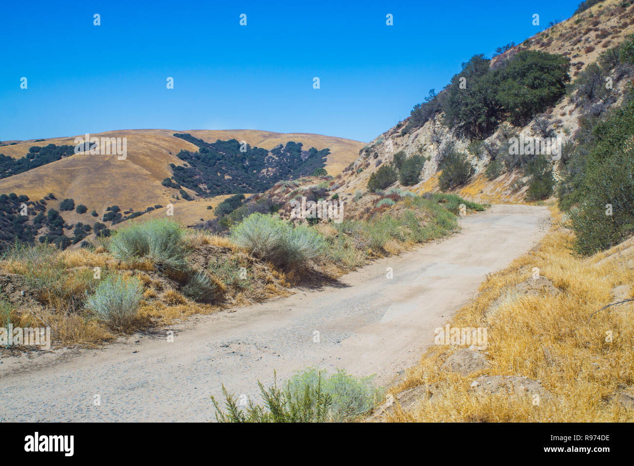 Dirt and gravel road leading through the mountain wilderness of southern California outside Los Angeles. - Stock Image