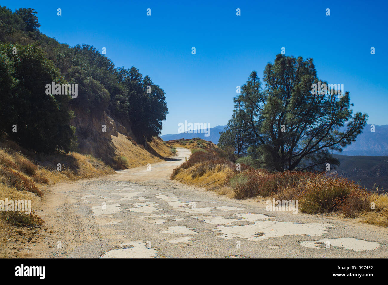 Rutted and pothole road leading into the mountains of southern California's Angeles National Forest. - Stock Image