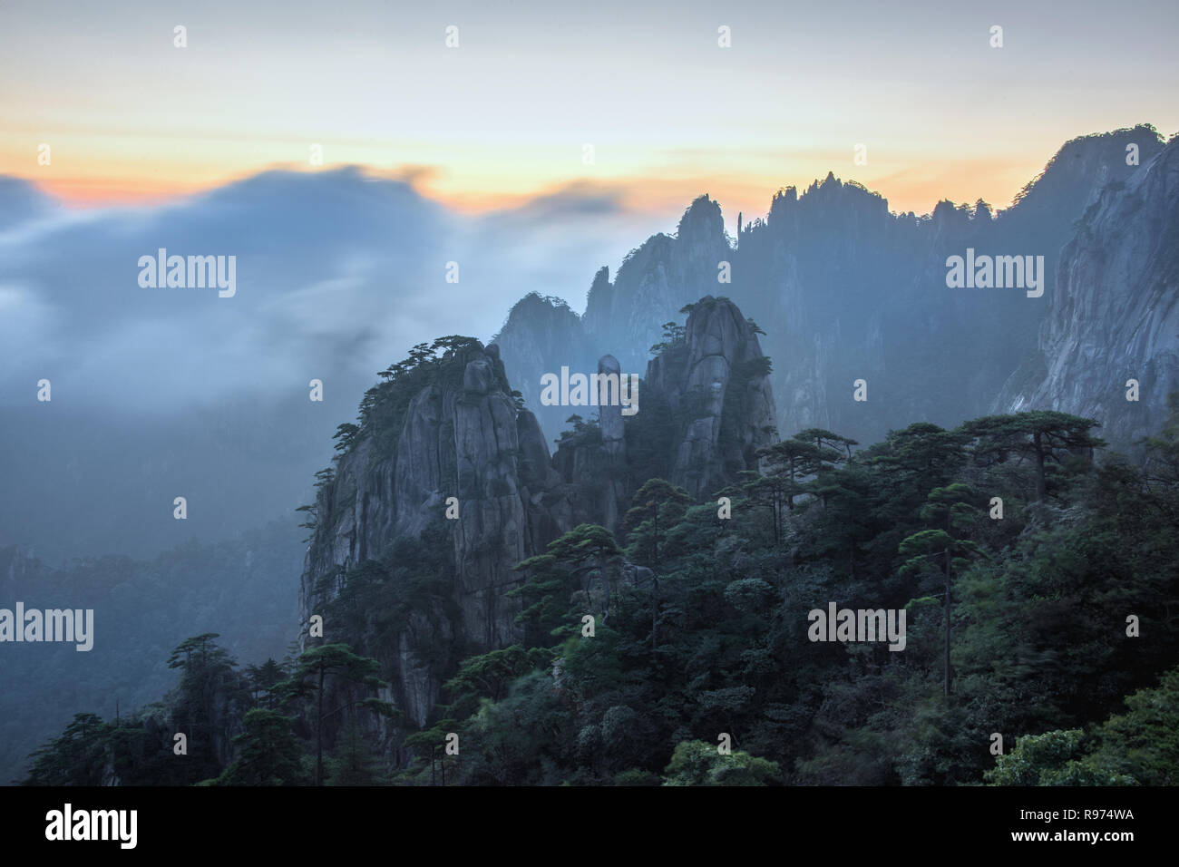 Huangshan pillars with blowing mists at sunrise, Anhui, China - Stock Image