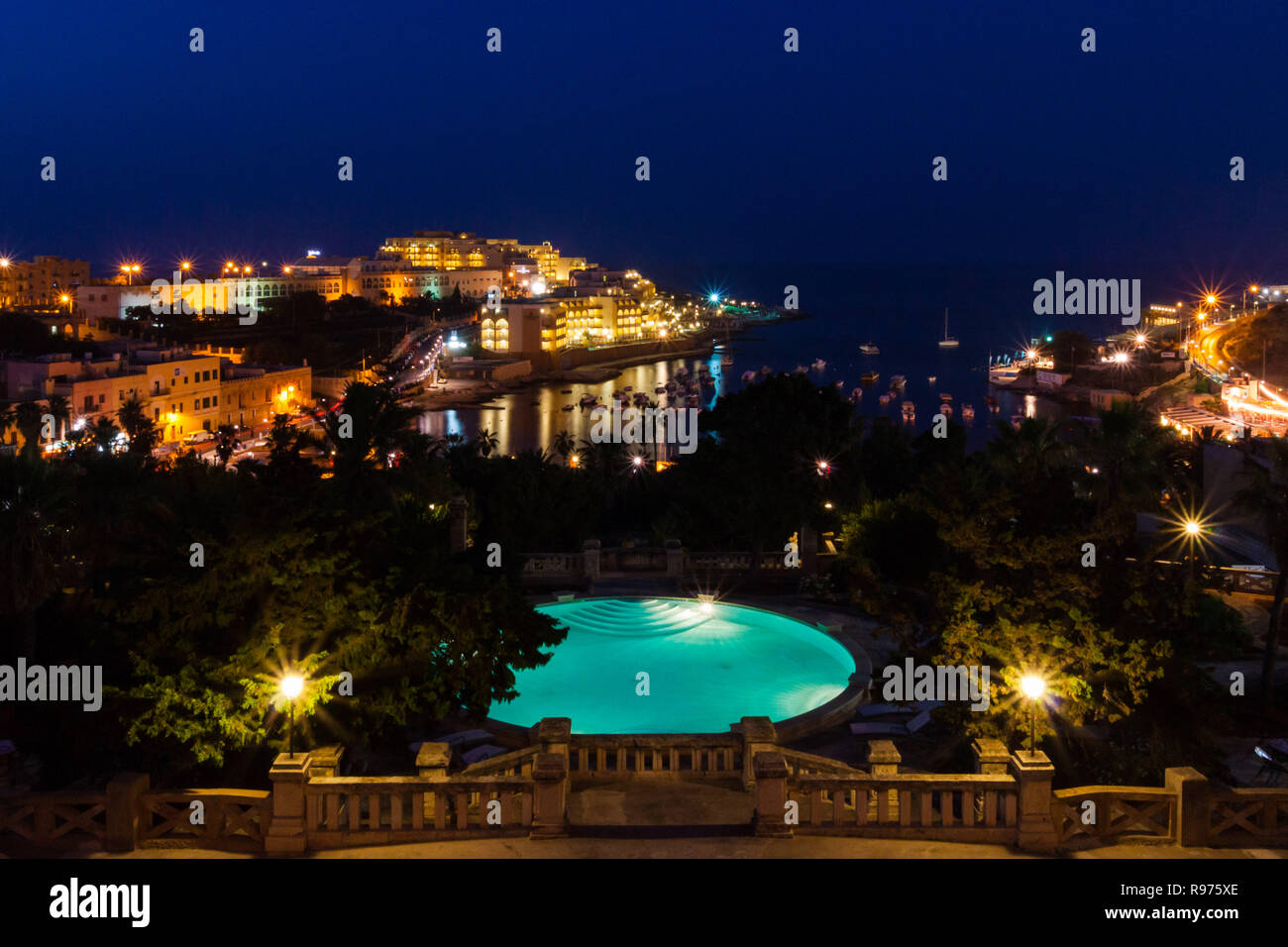 View of St. George's Bay seafront lights by night, with a blue luxury swimming pool and boats and yachts anchored. St Julian's (San Giljan), Central Region, Malta. Evening in Paceville district. - Stock Image