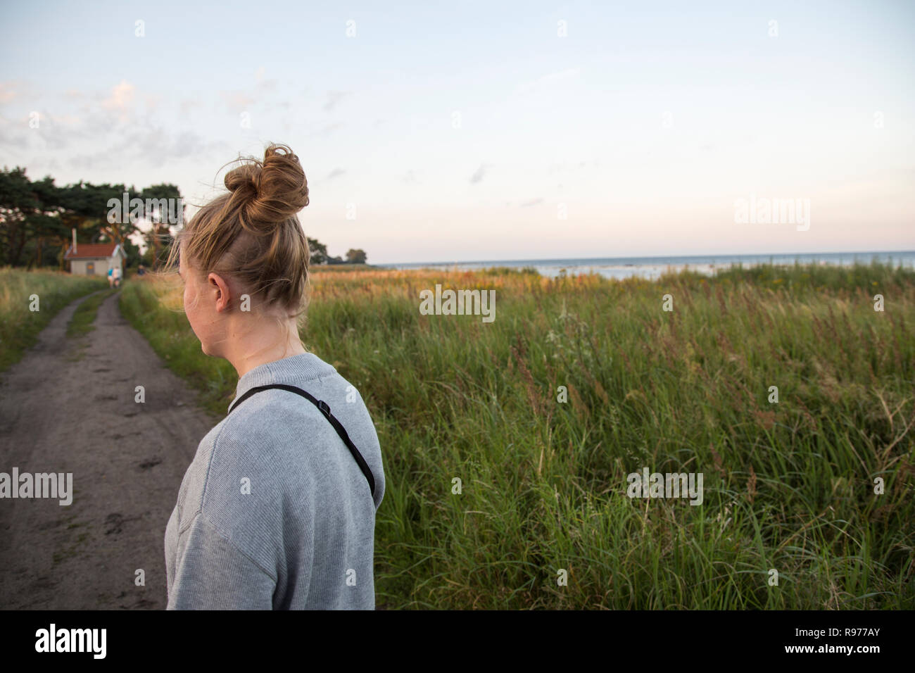 Young woman standing on an unpaved road in Ornahusen, Sweden - Stock Image