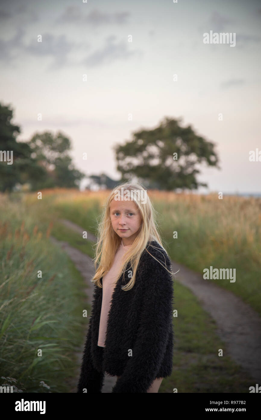 Girl standing in front of a unpaved road in Ornahusen, Sweden - Stock Image