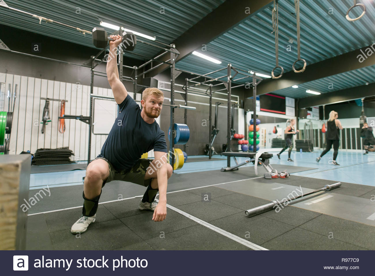 Young man lifting a dumbbell in a gym - Stock Image