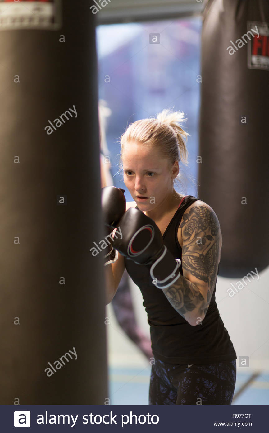 Young woman punching a boxing bag in a gym - Stock Image
