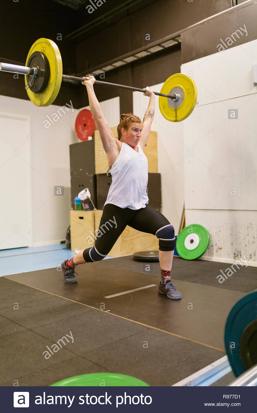 Young woman lifting a barbell in a gym - Stock Image