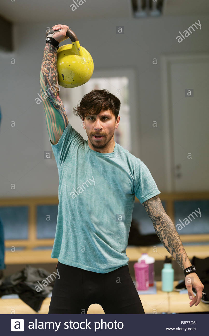Mid adult man lifting a kettlebell at a gym - Stock Image