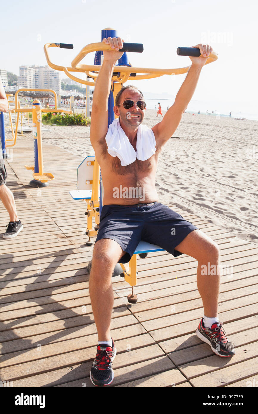 Mid adult man working out on a beach in Fuengirola, Spain - Stock Image
