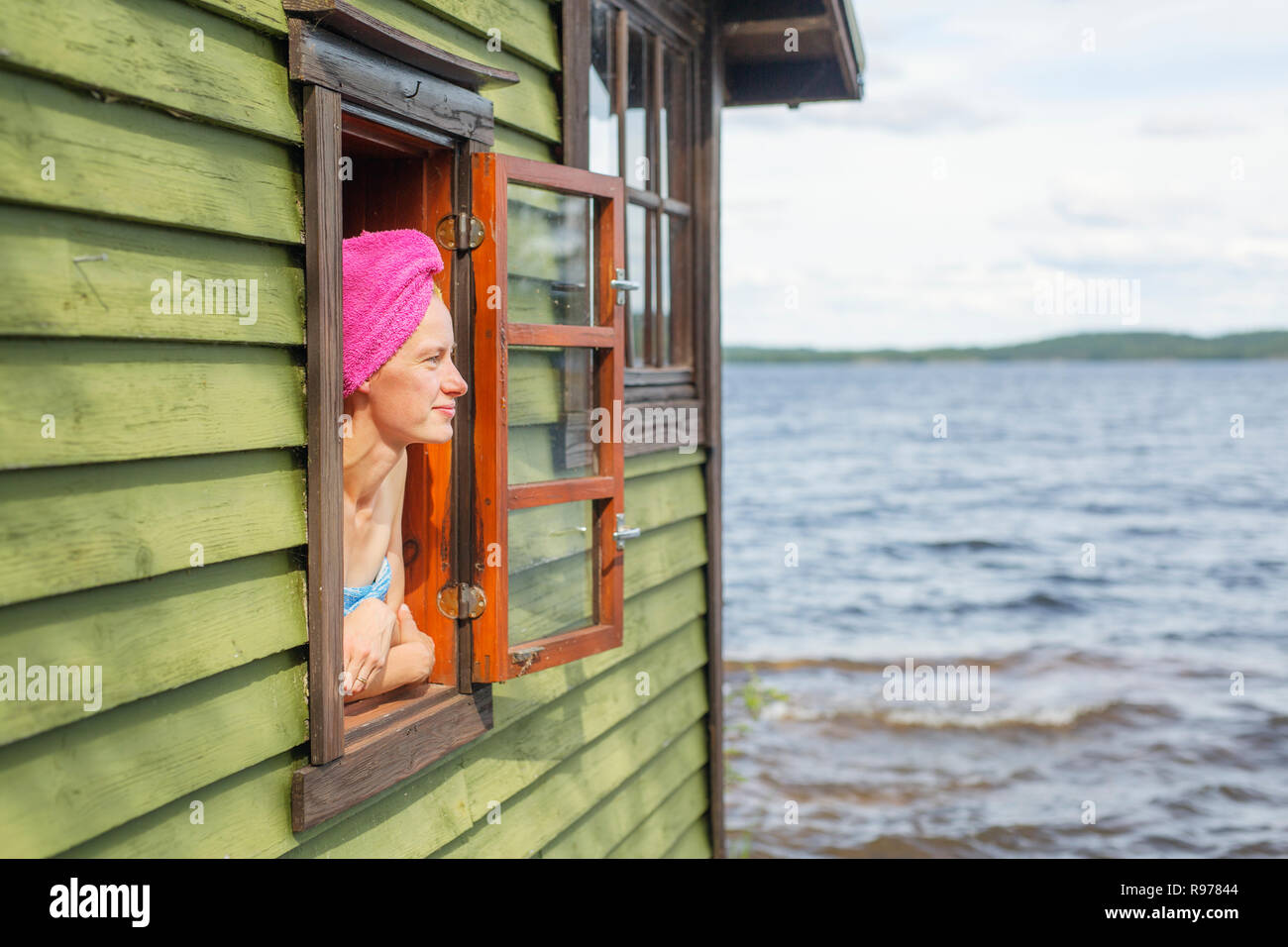 Mid adult woman looking out the window of a sauna in Finland - Stock Image