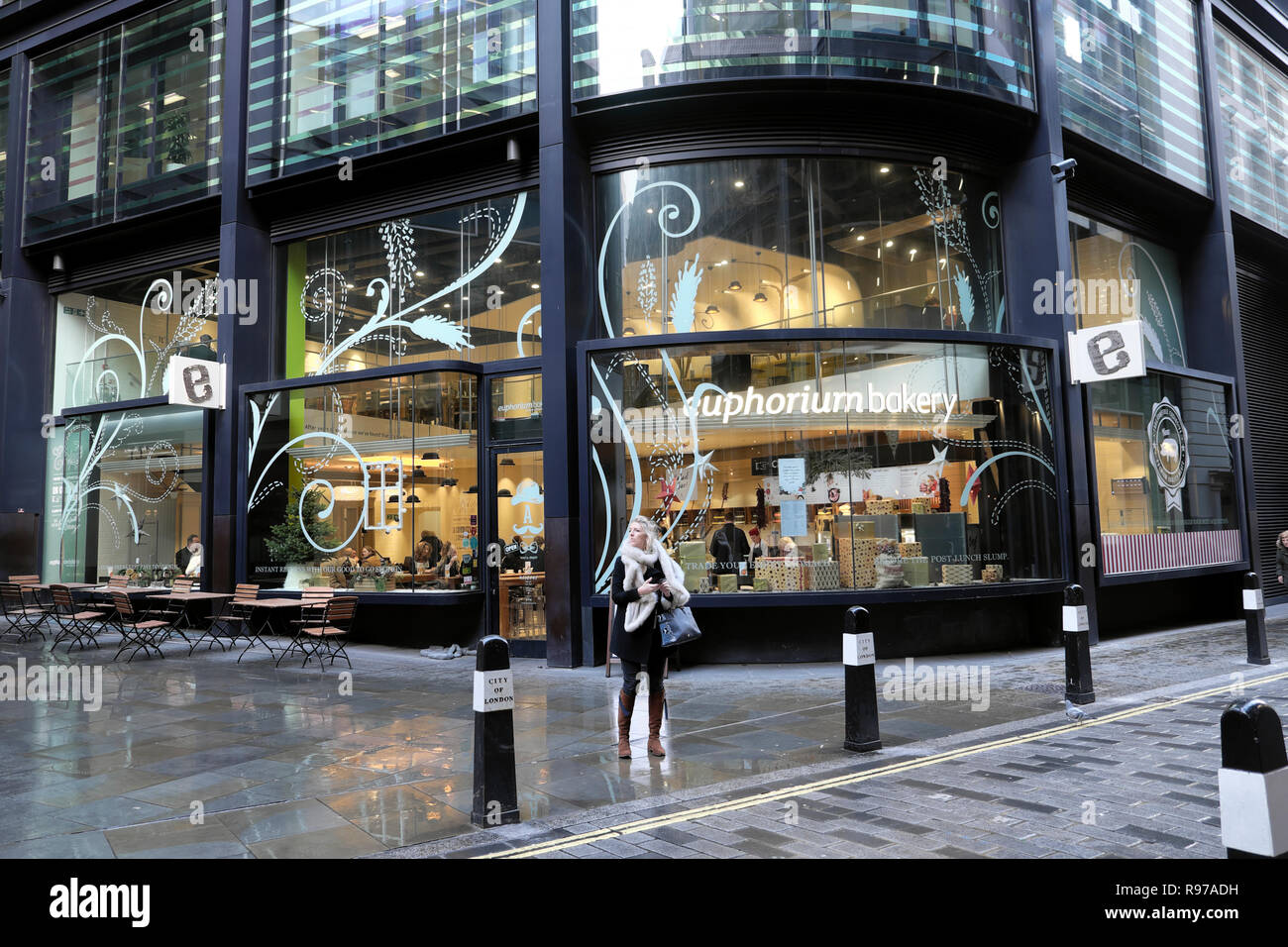 Euphorium Bakery and woman standing outside at Christmas time in Threadneedle Street City of London England UK  KATHY DEWITT - Stock Image