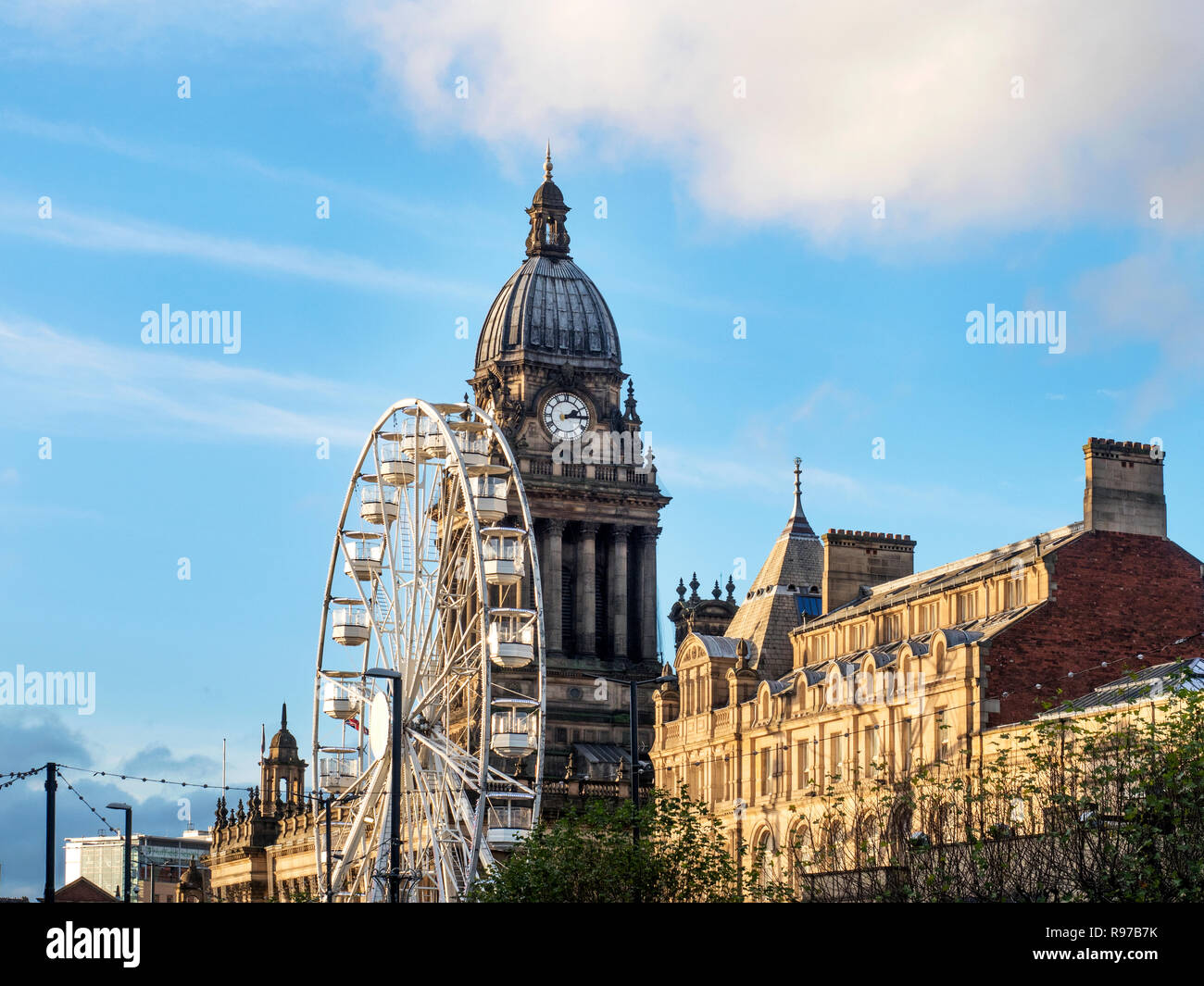Ferris wheel and the tower of Leeds Town Hall on The Headrow Leeds West Yorkshire England - Stock Image