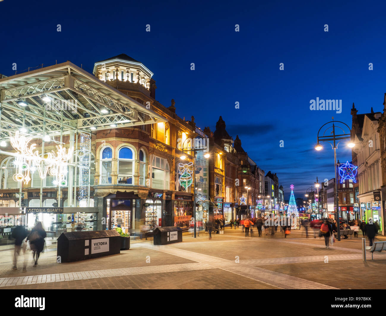 Victoria Quarter and Briggate shopping street busy at dusk at Chrsitmas in Leeds West Yorkshire England - Stock Image