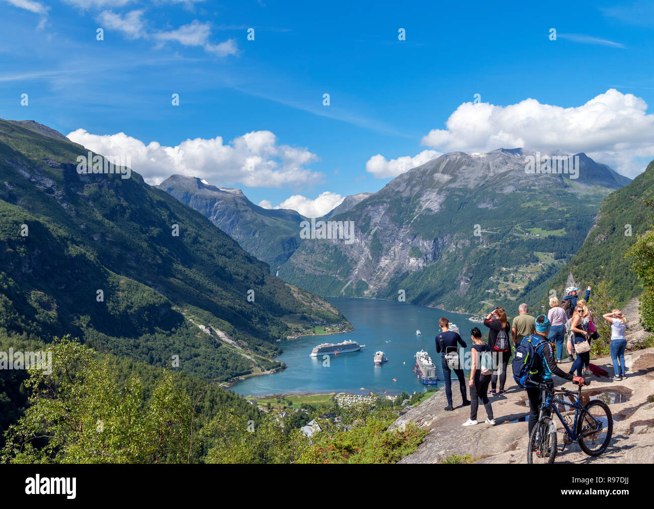 Tourists at the viewpoint overlooking the town of Geiranger and Geirangerfjord, Norway - Stock Image