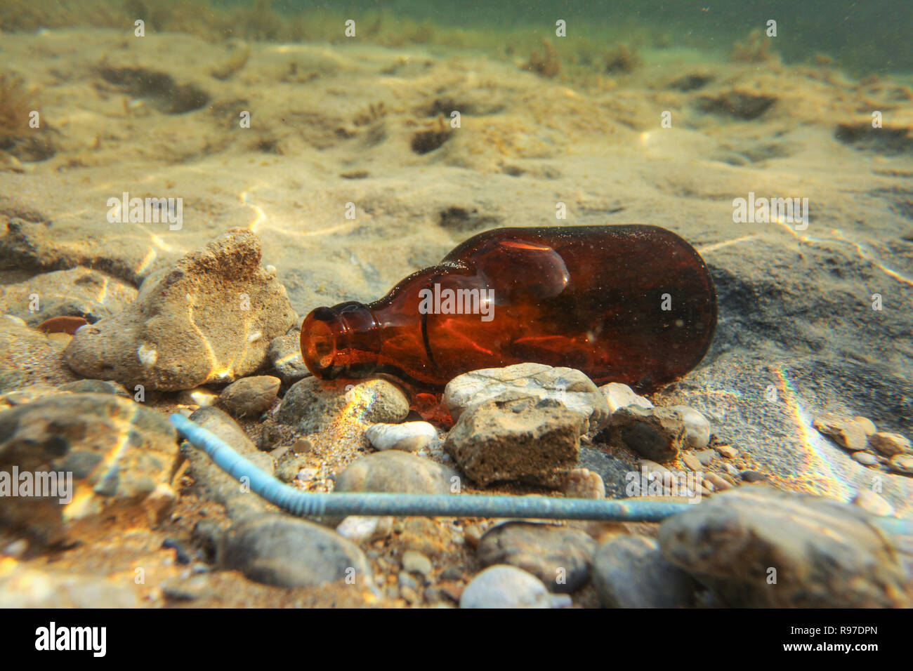 Small brown beer bottle and blue plastic straw on sandy sea bottom. Underwater photo, ocean littering concept. - Stock Image