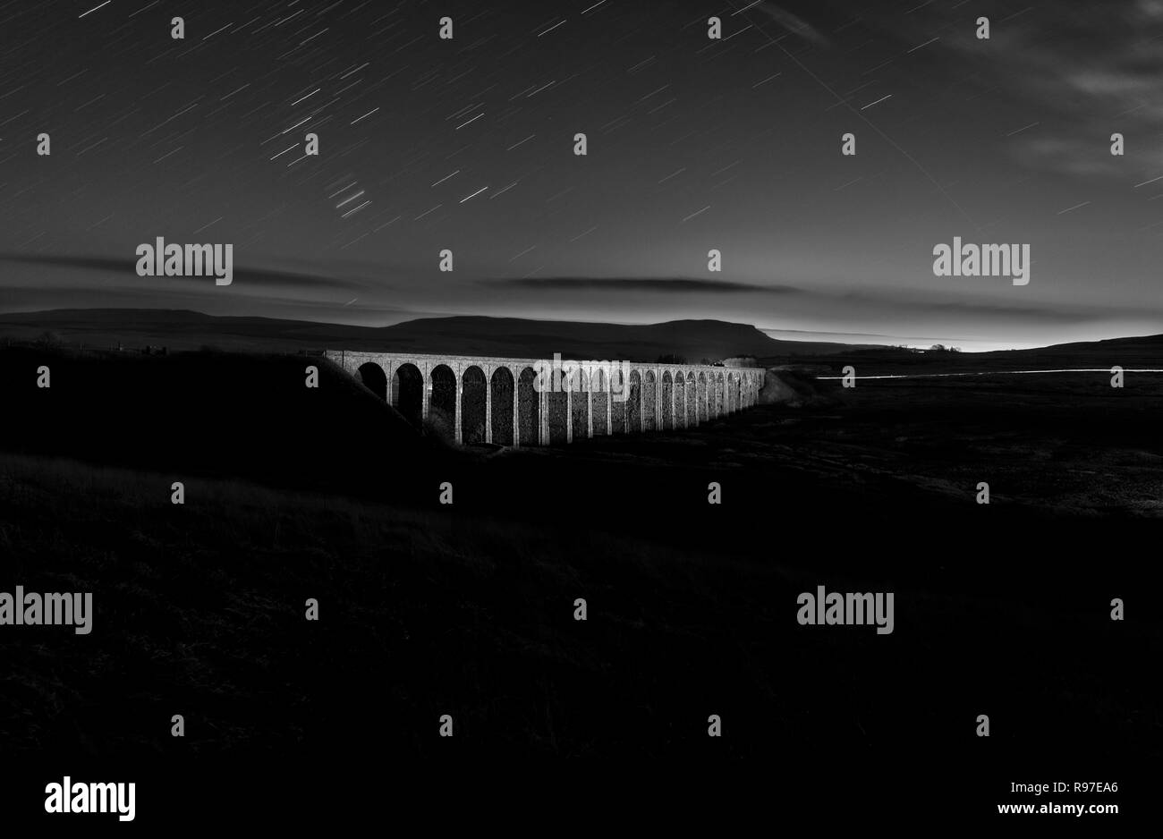 Ribblehead viaduct on the settle to Carlisle railway line at night floodlit by light painting with a torch. Penyghent is behind - Stock Image