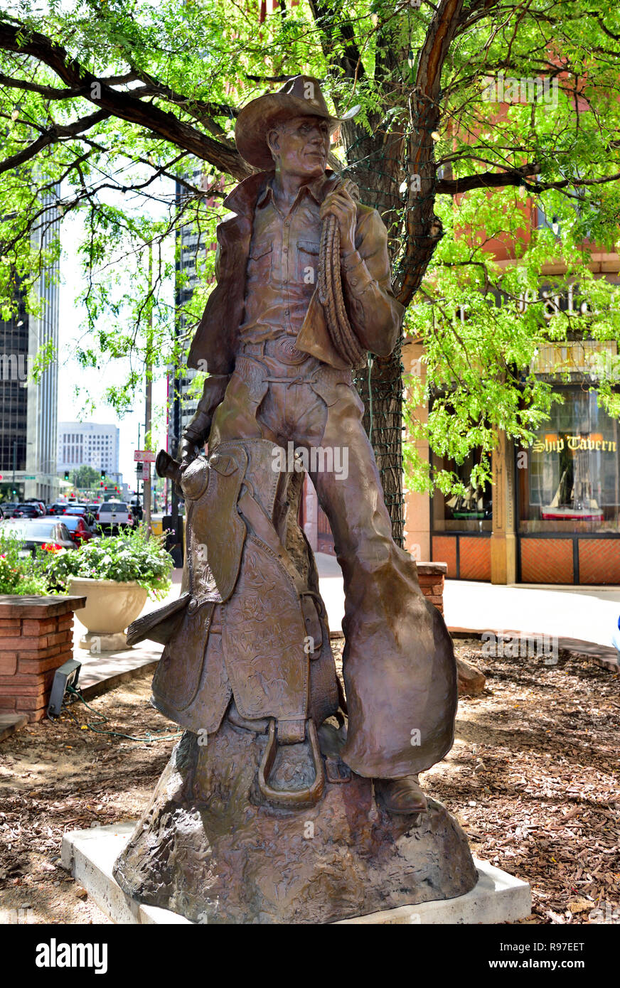 Statue of American Cowboy standing with saddle, lasso rope, chaps. National Western Stock Show, 2006, Denver Colorado - Stock Image