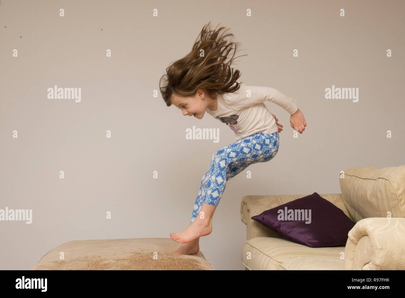 child, girl indoors leaping, jumping on furniture, sofa, being energetic, hyperactive, having fun, six years old, Stock Photo