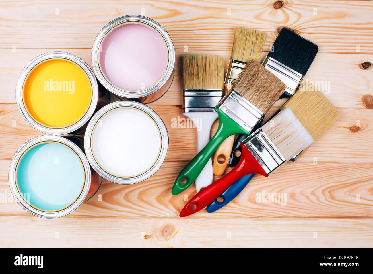 Four open cans of paint with brushes on natural wooden background. Yellow, white, pink, turquoise colors. Renovation concept. Stock Photo