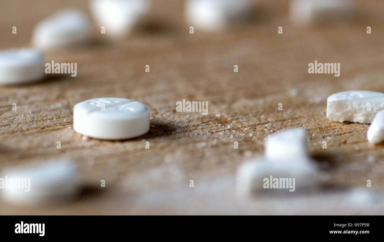 closeup view cutting white round pill by knife on wooden board. - Stock Image