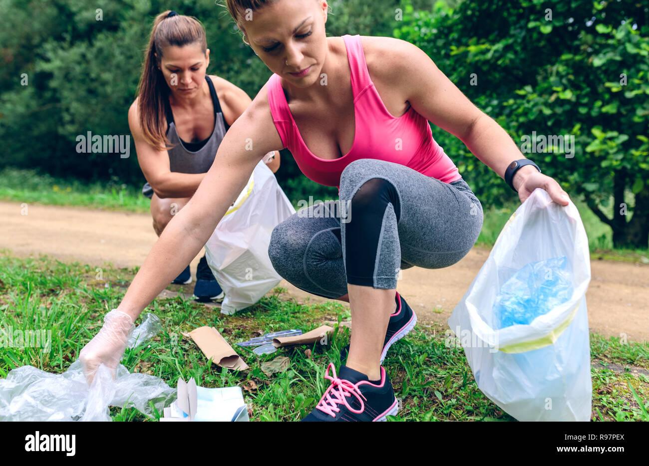 Women picking up trash doing plogging - Stock Image
