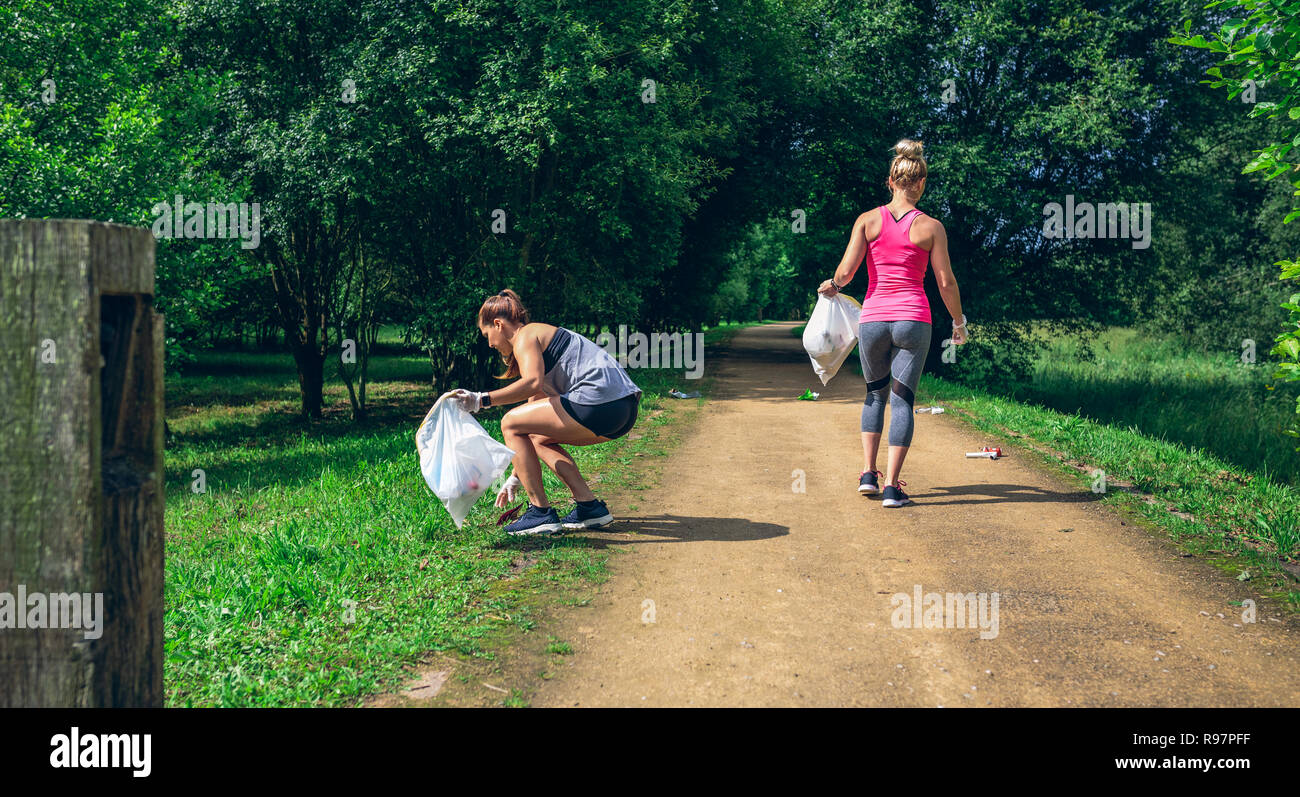 Two girls on back doing plogging - Stock Image