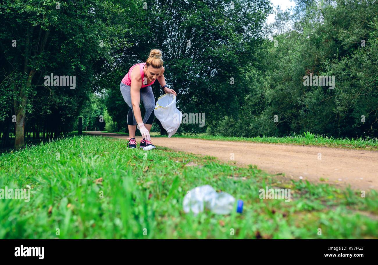 Girl picking up trash doing plogging - Stock Image