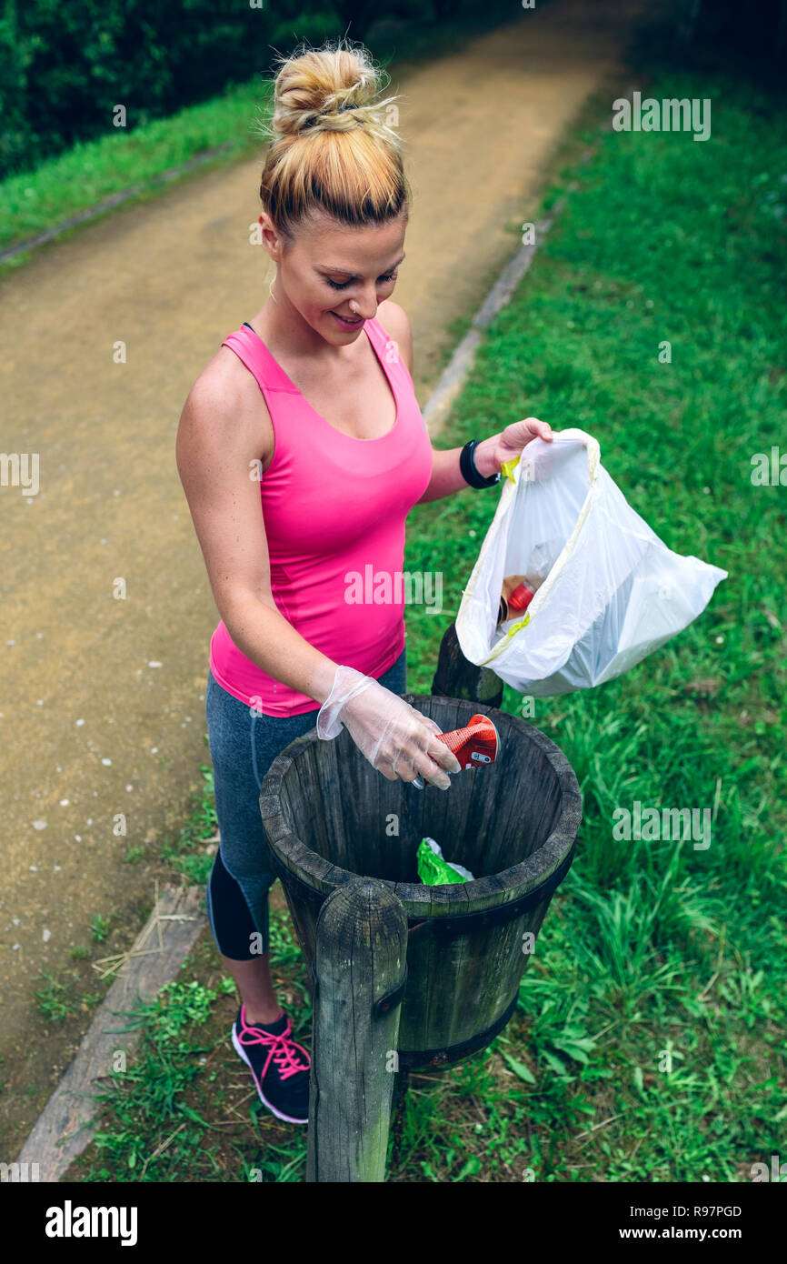Woman throwing garbage after plogging - Stock Image