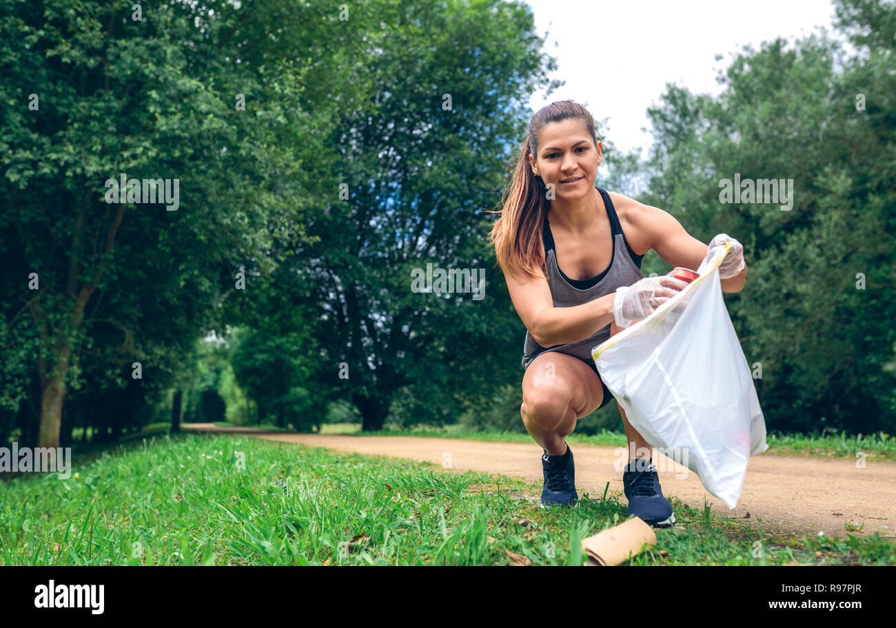 Girl with garbage bag doing plogging - Stock Image