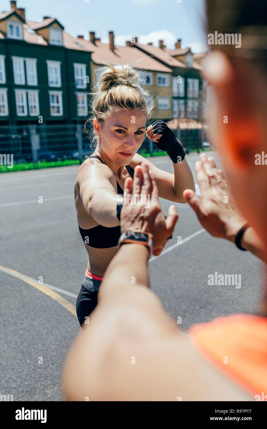 Sportswoman training boxing with her trainer - Stock Image