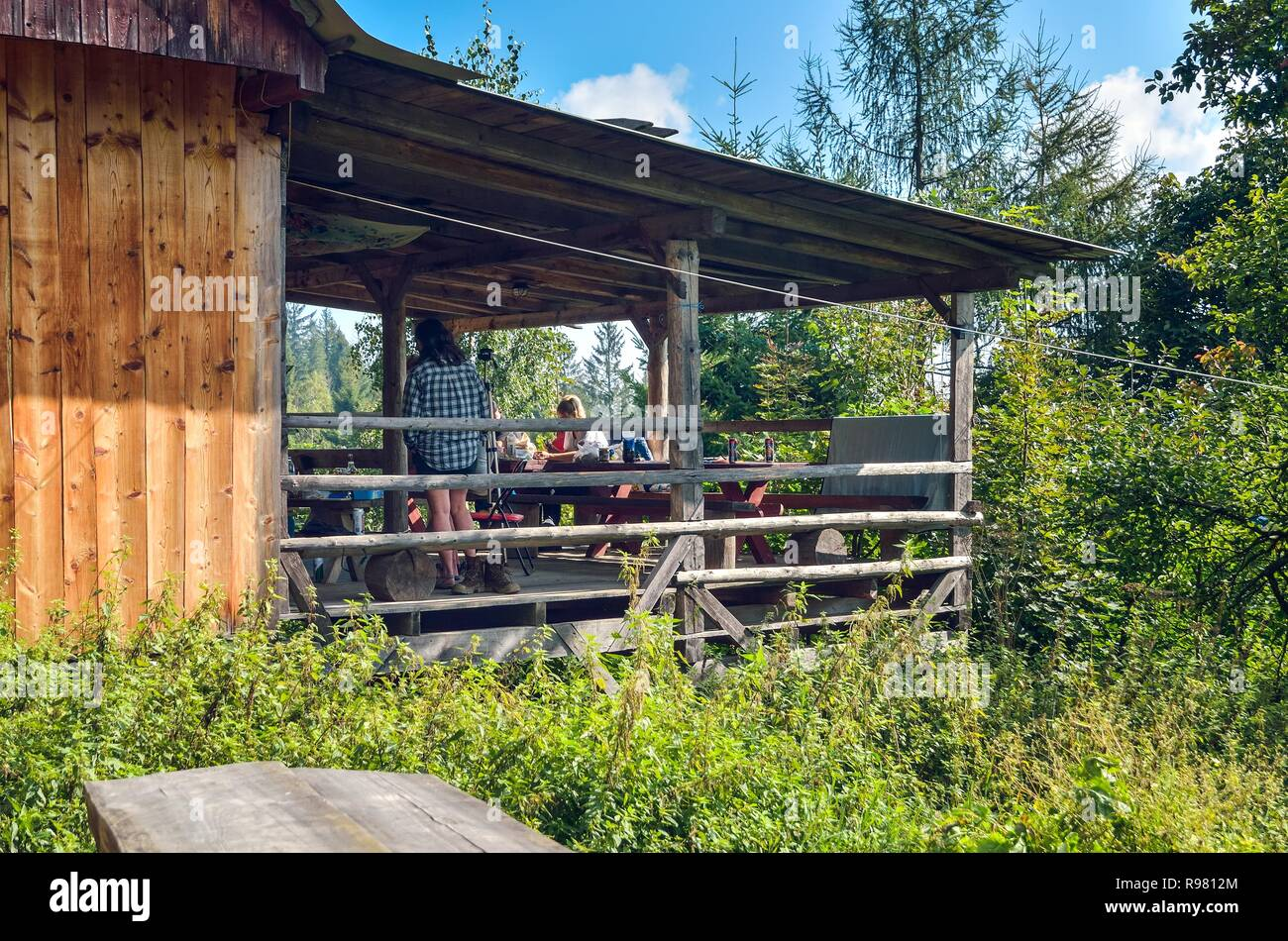 BESKIDS, POLAND - SEPTEMBER 9, 2018: Tourists on the porch in front of a mountain hostel in the Beskids in Poland. - Stock Image