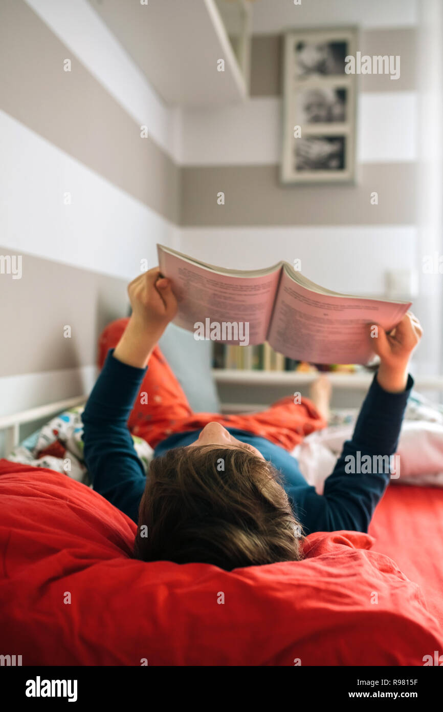 Boy reading on his bed - Stock Image