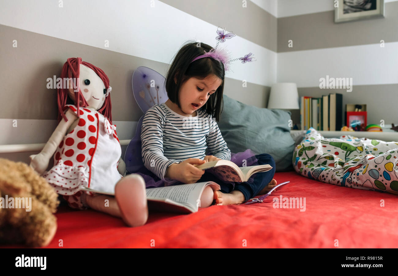 Girl disguised reading a book to her doll - Stock Image