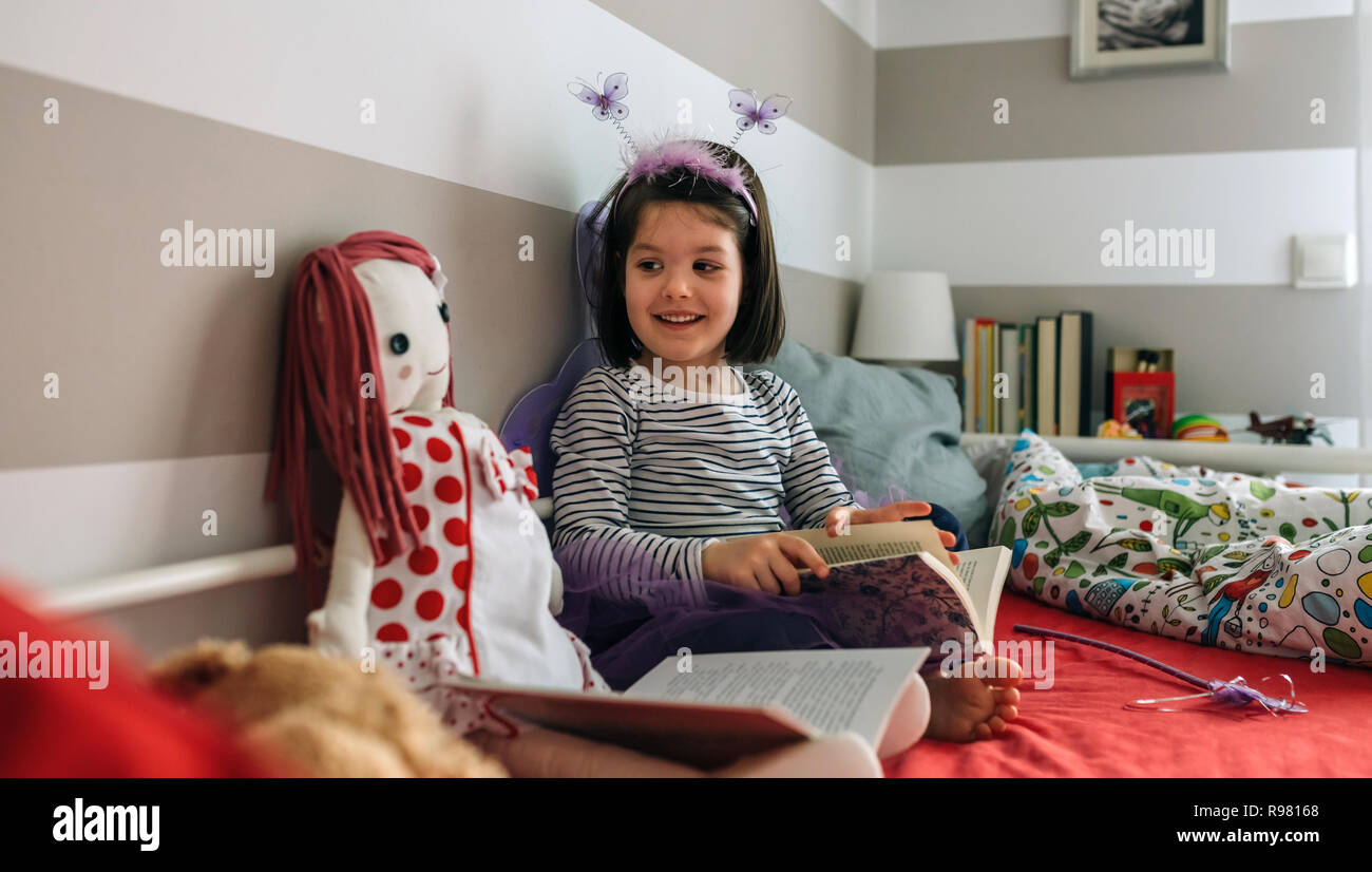 Girl disguised as a butterfly reading with her doll - Stock Image
