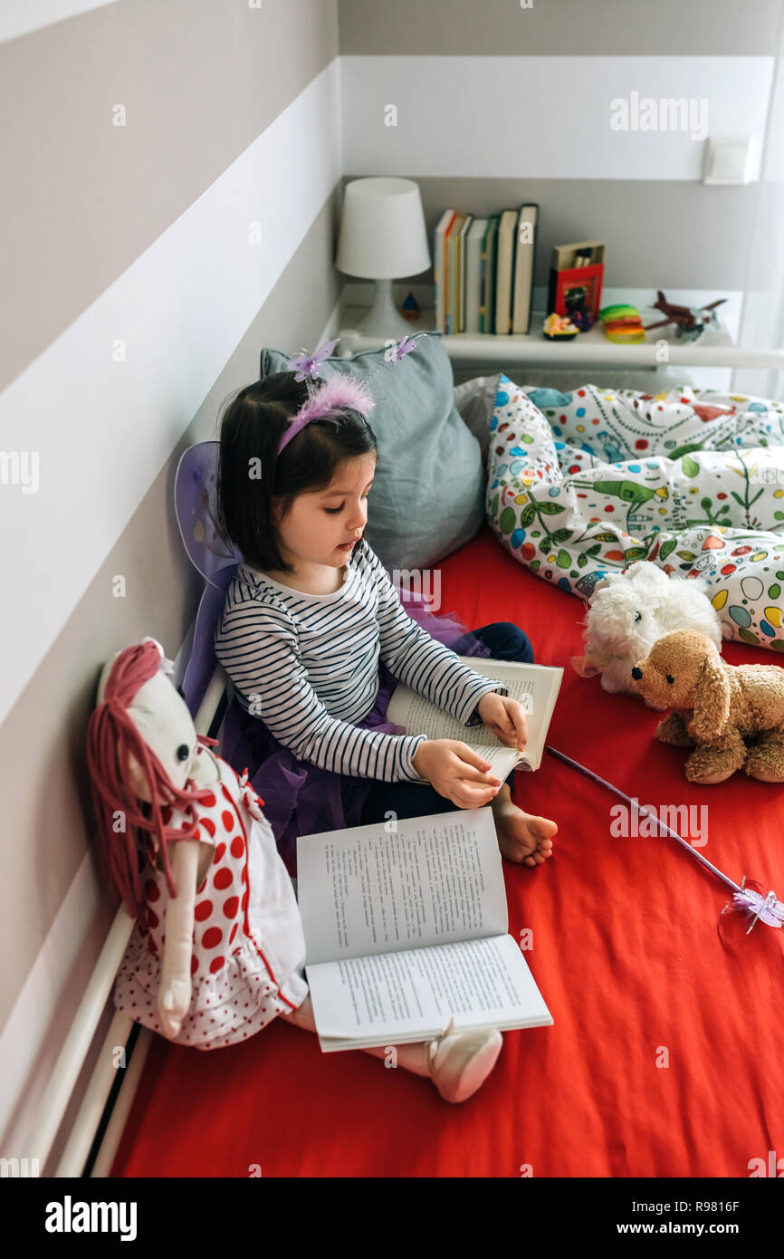 Girl disguised reading a book to her toys - Stock Image