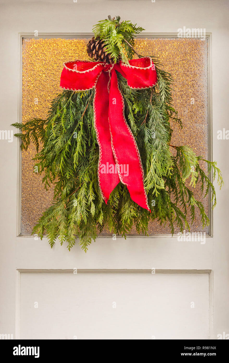 Vintage Style Red Bow Tied To Natural Green Evergreen Tree Christmas  Wreath, Hanging On Window Pane In Old Antique White Painted Antique Door.