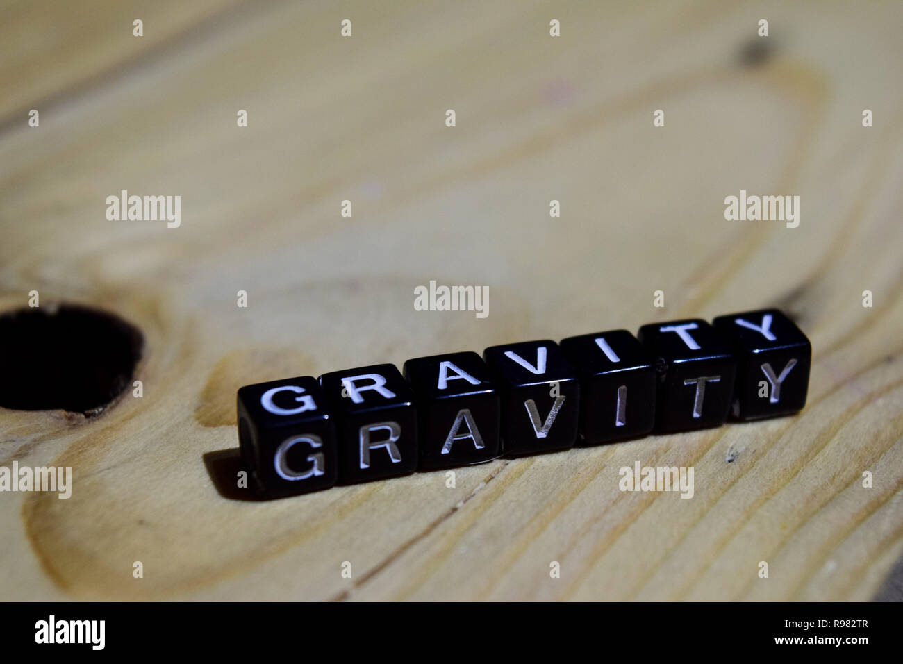Gravity written on wooden blocks. Inspiration and motivation concepts. Cross processed image on Wooden Background - Stock Image