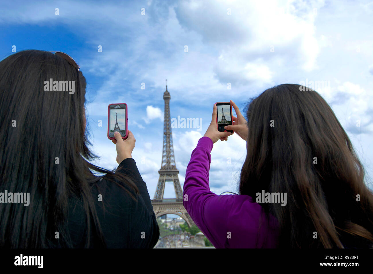 Tourists photographing Eiffel tower with his smartphone, Paris, Ile de France, France - Stock Image